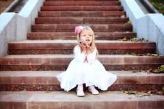 Schönes Mädchen, das auf der Treppe sitzt stockfotografie
