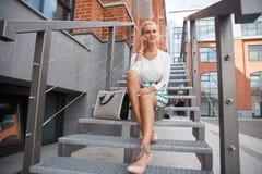 Schönes Mädchen, das auf der Treppe sitzt Stockfoto