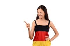 Schönes Mädchen, das auf die Seite zeigt. Attraktives Mädchen mit Deutschland-Flaggenbluse. Lizenzfreie Stockfotografie