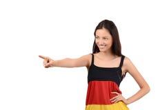 Schönes Mädchen, das auf die Seite zeigt. Attraktives Mädchen mit Deutschland-Flaggenbluse. Lizenzfreies Stockfoto