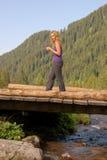 Schönes Mädchen, das auf eine hölzerne Brücke geht stockfoto