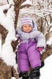 Schönes Mädchen, das auf einem Baumzweig im Freien sitzt Stockfoto