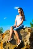 Schönes Mädchen, das auf einem Felsen sitzt Stockfoto