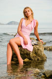 Schönes Mädchen, das auf einem Felsen am Strand sitzt Stockfoto