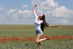 Schönes Mädchen, das auf einem Gebiet mit Mohnblumen springt Stockbild