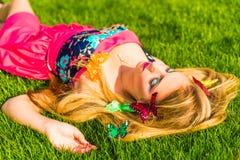 Schönes Mädchen, das auf einem Gras im Park liegt Lizenzfreie Stockfotos