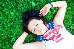 Schönes Mädchen, das auf einem Gras liegt Stockbild