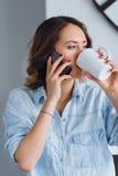 Schönes Mädchen, das auf einem Handy und einem trinkenden Tee spricht Stockbild
