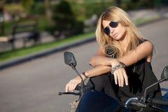 Schönes Mädchen, das auf einem Motorrad aufwirft Stockbild