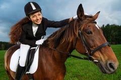 Schönes Mädchen, das auf einem Pferd sitzt Stockfoto