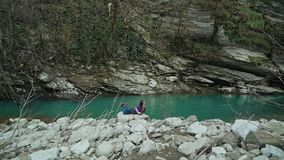 Schönes Mädchen, das auf einem Stein auf dem Ufer von einem Türkissee in den Bergen, der allgemeine Plan liegt stock footage