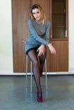 Schönes Mädchen, das auf einem Stuhl sitzt Stockbilder