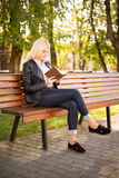 Schönes Mädchen, das auf einer Bank sitzt und ein Buch liest Stockfoto