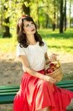 Schönes Mädchen, das auf einer Bank sitzt und einen Korb mit appl hält Lizenzfreies Stockfoto