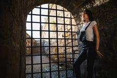 Schönes Mädchen, das auf einer Gefängnismauer sich lehnt Lizenzfreies Stockbild
