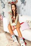 Schönes Mädchen, das auf einer weißen Couch sitzt Viele Spielwaren Christma Stockbilder
