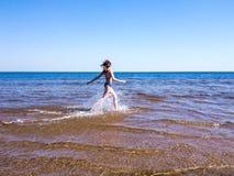 Schönes Mädchen, das auf glänzendem Wasser läuft lizenzfreie stockfotos