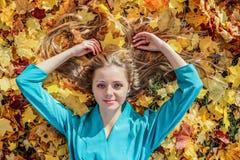 Schönes Mädchen, das auf Gras mit Ahornblättern im Herbst liegt Lizenzfreie Stockbilder