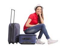 Schönes Mädchen, das auf ihrem Gepäck sitzt Stockfoto