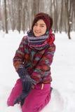 Schönes Mädchen, das auf Schnee sitzt Lizenzfreie Stockbilder