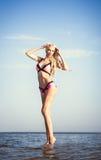 Schönes Mädchen, das auf Seehintergrund aufwirft Stockfotografie
