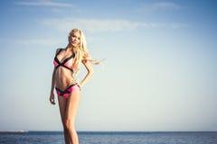 Schönes Mädchen, das auf Seehintergrund aufwirft Lizenzfreies Stockbild