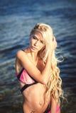 Schönes Mädchen, das auf Seehintergrund aufwirft Lizenzfreie Stockfotos