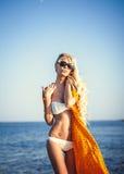 Schönes Mädchen, das auf Seehintergrund aufwirft Stockfoto