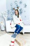 Schönes Mädchen, das auf Sofa in einem Reinraum sitzt Lizenzfreie Stockfotos