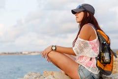Schönes Mädchen, das auf Stein- und schauendem ruhigem See stillsteht Lizenzfreies Stockbild