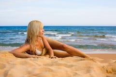 Schönes Mädchen, das auf Strand liegt Stockbilder