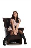 Schönes Mädchen, das auf Stuhl sitzt Stockfotografie