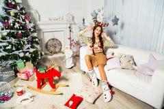 Schönes Mädchen, das auf weißem Sofa nahe dem Weihnachtsbaum sitzt A Stockfoto