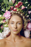 Schönes Mädchen, das in den Blumen liegt Lizenzfreies Stockfoto
