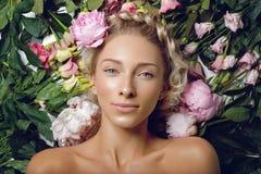 Schönes Mädchen, das in den Blumen liegt Stockfotografie