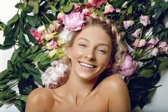 Schönes Mädchen, das in den Blumen liegt Lizenzfreie Stockfotografie