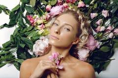 Schönes Mädchen, das in den Blumen liegt Stockfotos