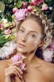 Schönes Mädchen, das in den Blumen liegt Stockfoto