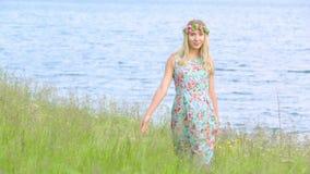 Schönes Mädchen, das in die Wiese trägt Blumenkranz geht Junger Erwachsener Tragendes stilvolles Kleid mit Blumendruck stock footage