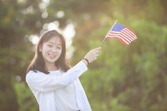 Schönes Mädchen, das draußen amerikanische Flagge am Sommertag hält ind lizenzfreies stockbild