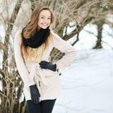 Schönes Mädchen, das draußen aufwirft und nahe in einer Winterzeit lächelt Stockbilder