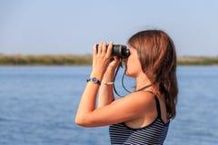 Schönes Mädchen, das durch Ferngläser auf dem Fluss schaut stockbilder