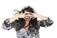 Schönes Mädchen, das durch ihre Finger lookiing ist Lizenzfreies Stockfoto