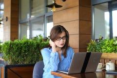 Schönes Mädchen, das durch Laptop am Café grast lizenzfreies stockbild