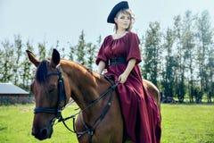 Schönes Mädchen, das ein braunes Pferd reitet lizenzfreie stockbilder