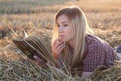 Schönes Mädchen, das ein Buch bei Sonnenuntergang in einem Heuschober liest lizenzfreie stockfotos