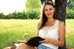 Schönes Mädchen, das ein Buch im Garten im Sommer liest Stockbild