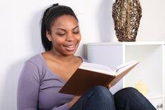 Schönes Mädchen, das ein Buch lesend lächelt und genießt Stockbilder
