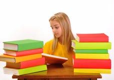 Schönes Mädchen, das ein Buch umgeben durch Bücher liest Stockfotos
