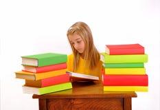 Schönes Mädchen, das ein Buch umgeben durch Bücher liest Lizenzfreie Stockfotografie